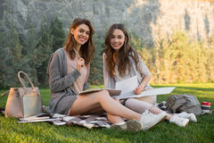 Cheerful young two women sitting outdoors in park writing notes. Picture of cheerful young two women sitting outdoors in park writing notes. Looking camera Stock Photography