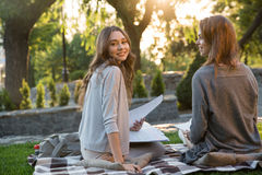 Cheerful young two women sitting outdoors in park writing notes. Picture of cheerful young two women sitting outdoors in park writing notes. Looking camera Royalty Free Stock Images