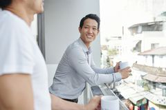 Businessman listening to joke of colleague stock photo