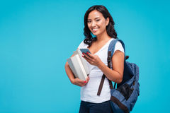 Cheerful young vietnamese girl holding backpack and books using smartphone Royalty Free Stock Photography