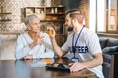 Cheerful young volunteer suggesting useful vitamins to a pensioner. Useful vitamins. Young experienced cheerful volunteer looking friendly while showing new Royalty Free Stock Photo
