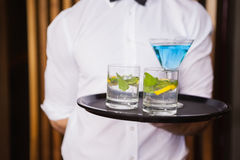 Cheerful young waiter holding tray with cocktails Royalty Free Stock Images
