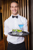 Cheerful young waiter holding tray with cocktails. In a bar Stock Image
