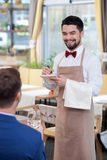 Cheerful young waiter is serving a customer. Attractive male cafe worker is receiving an order. He is standing and smiling. The men is writing down notes. The Stock Images