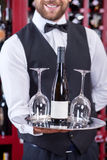 Cheerful young waiter is serving wineglasses for. Close up of cute male sommelier standing and posing in restaurant. He is holding tray with two glasses and royalty free stock photos