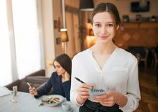 Cheerful young waitress stand and look straight on camera. She smile and write order into notebook. Female customer sit royalty free stock photography