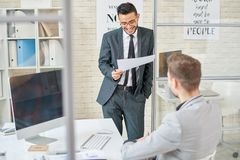Working Process at Open Plan Office. Cheerful young white collar worker wearing classical suit studying document while standing at modern open plan office, his Stock Photo