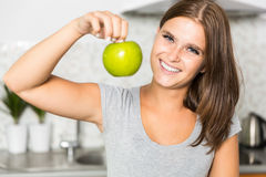 Cheerful young woman with an apple. In kitchen Royalty Free Stock Photos