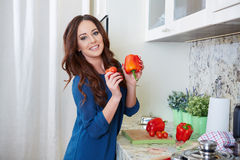 Cheerful young woman in apron on modern kitchen Stock Images