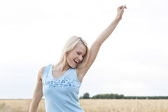 Cheerful young woman with arm raised standing against clear sky Stock Images