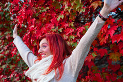 Cheerful young woman with autumn leafs in front of f Royalty Free Stock Photos