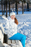 Cheerful young woman on the bench with hands up, winter season Royalty Free Stock Image