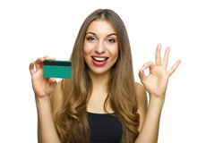 Cheerful young woman in black dress holding bank card and showing OK sign isolated on a white background.  stock photo