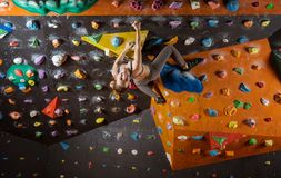 Cheerful young woman bouldering in climbing gym Royalty Free Stock Photo