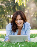 Cheerful, young woman browsing her tablet in the park stock images