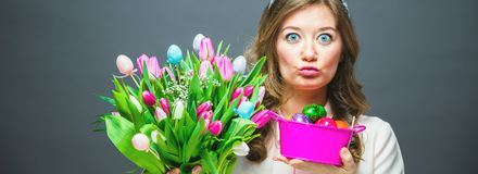 Cheerful young woman with bunny ears and Easter egg basket and tulips Flowers Looking at camera stock image