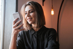 Cheerful young woman in cafe chatting by her phone. Portrait of cheerful young woman sitting at the table in cafe and chatting by her phone royalty free stock photos