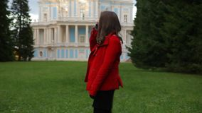 Cheerful young woman calls her friend by mobile in an autumn park. Beautiful girl stands in a picturesque autumn park, dressed in red coat, black leggings, and stock video