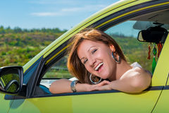 Cheerful young woman in a car royalty free stock photography