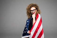 Cheerful young woman in casual clothes and glasses is covered in the American flag and smiling on gray background Stock Image