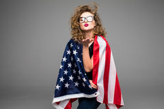 Cheerful young woman in casual clothes and glasses is covered in the American flag and smiling on gray background Royalty Free Stock Photography