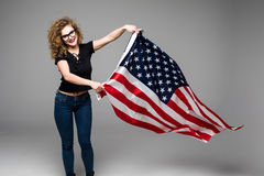 Cheerful young woman in casual clothes is wave the American flag and smiling on gray background Royalty Free Stock Image