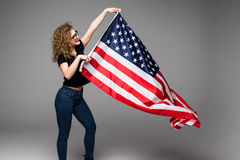 Cheerful young woman in casual clothes is wave the American flag and smiling on gray background Stock Photos