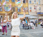 Cheerful young woman catching the soap bubbles Stock Images