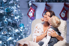 Cheerful young woman and child are celebrating. Beautiful mother and her son are sitting on chair near New Year fir-tree. They are embracing. The boy is kissing Stock Photography