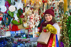 Cheerful young woman choosing Christmas decoration Stock Photography