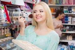 Cheerful young woman choosing face powder Royalty Free Stock Image