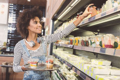 Cheerful young woman is choosing foodstuffs stock photography