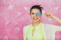 Cheerful young woman with colorful lollipops over pink backgroun. D. Young girl have fun with candies and close one eye with caramel sweets. Copy space Royalty Free Stock Photo