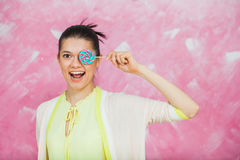 Cheerful young woman with colorful lollipops over pink backgroun. D. Young girl have fun with candies and close one eye with caramel sweets. Copy space Stock Photos