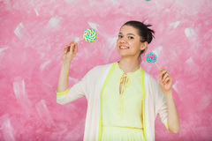Cheerful young woman with colorful lollipops over pink backgroun. D. Young girl have fun with candies. Holiday concept Royalty Free Stock Photos