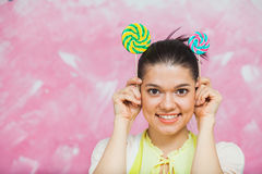 Cheerful young woman with colorful lollipops over pink backgroun. D. Young girl have fun with candies and make mouse ears with caramel sweets. Copy space Royalty Free Stock Image
