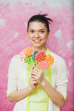 Cheerful young woman with colorful lollipops over pink backgroun. D. Pretty girl with bouquet of sweet caramel candies. Holiday concept. Vertical shot Royalty Free Stock Photos
