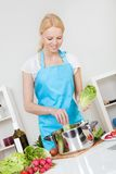 Cheerful young woman cooking Royalty Free Stock Images