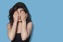 Cheerful young woman covering her face against blue background Stock Photos