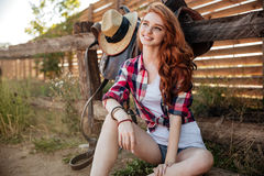 Cheerful young woman cowgirl sitting and smiling outdoors Royalty Free Stock Images