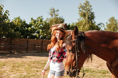 Cheerful young woman cowgirl walking wit her horse on ranch Stock Images