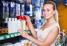 Cheerful young woman customer choosing paint medium in bottle in Royalty Free Stock Photo