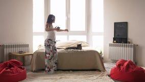 Cheerful young woman dancing in pajamas at home having fun listening to music wearing headphones enjoying weekend stock footage