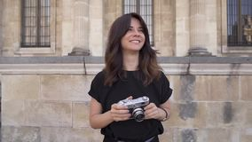 f925ede7 Cheerful young woman with dark hair in black t-shirt taking photos. Slow  motion