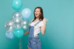 Cheerful young woman in denim clothes blinking, pointing thumb aside celebrating hold colorful air balloons isolated on. Blue turquoise wall background stock photos