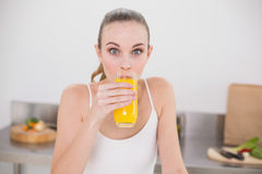 Cheerful young woman drinking glass of orange juice Stock Image