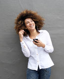 Cheerful young woman with earphones and smart phone Royalty Free Stock Images