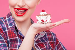 Cheerful young woman is eating tasty food. I want to eat this now. Pretty pin-up girl is holding a piece of sweet cake. She is licking her lips with tongue and Royalty Free Stock Photos
