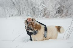 Cheerful young woman embracing with female caucasian shepherd dog on snow-covered field in frosty winter day.  royalty free stock image