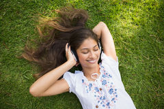 Cheerful young woman enjoying music in park Stock Image